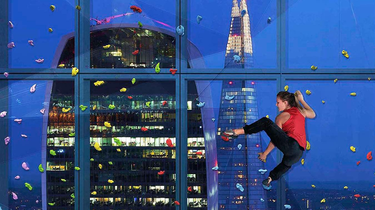 A climber on the transparent climbing wall with views of the London skyline