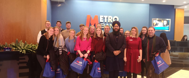 A group of smiling people enjoying a company visit at Metro Bank